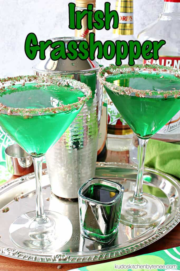 A vertical title text overlay graphic image of two bright green Irish Grasshopper Cocktails along with bottles of alcohol in the background.