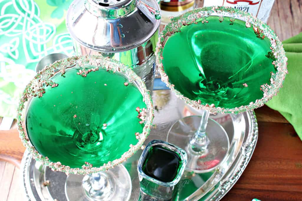 An overhead horizontal photo looking into two martini glasses filled with green Irish Grasshopper Cocktails on a silver platter.