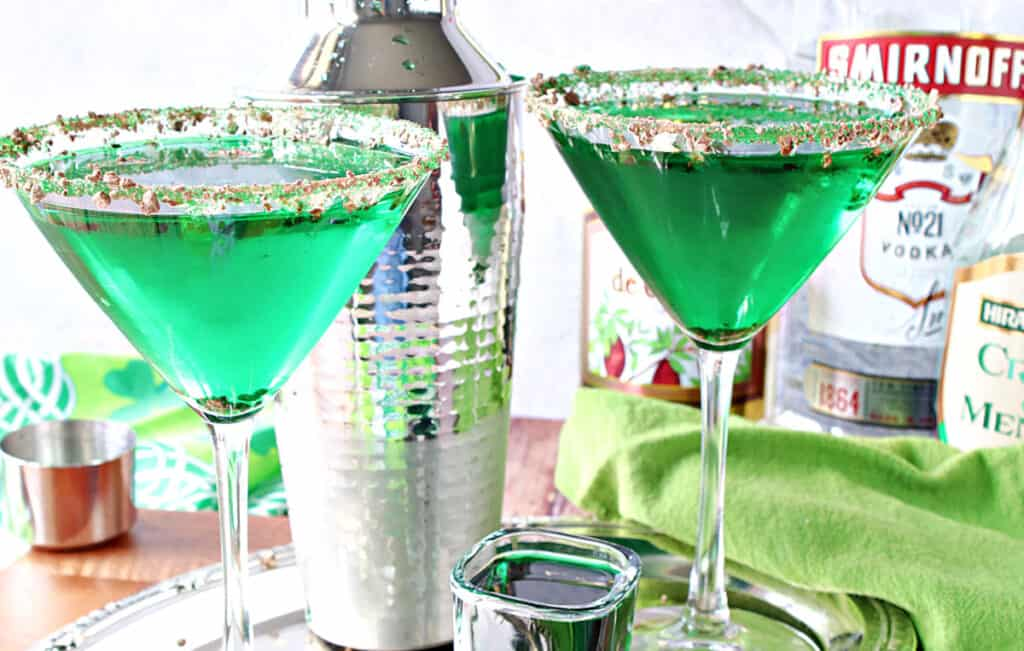 Two right green Irish Grasshopper Cocktails in martini glasses along with a shot glass filled with crème de menthe and a cocktail shaker in the background.
