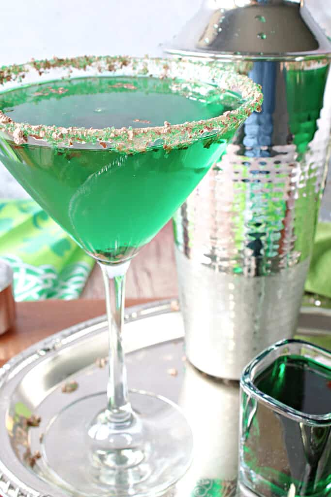 A vertical closeup photo of a martini glass filled with a green Irish Grasshopper Cocktail, and a cocktail shaker on a silver platter.