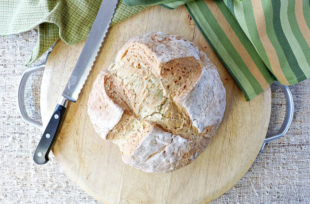 A direct overhead photo of a loaf of Irish Soda Bread with Caraway and Dill on a wooden cutting board with a serrated knife and some green napkins.