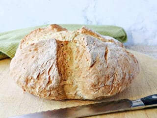 A whole loaf of Irish Soda Bread with Caraway and Dill on a wooden cutting board with a knife.