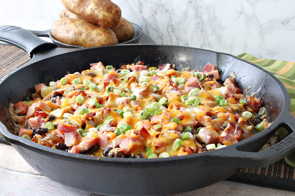 A horizontal photo of a black cast iron skillet filled with cheesy Loaded Skillet Potatoes topped with scallions along with some russet potatoes in the background.