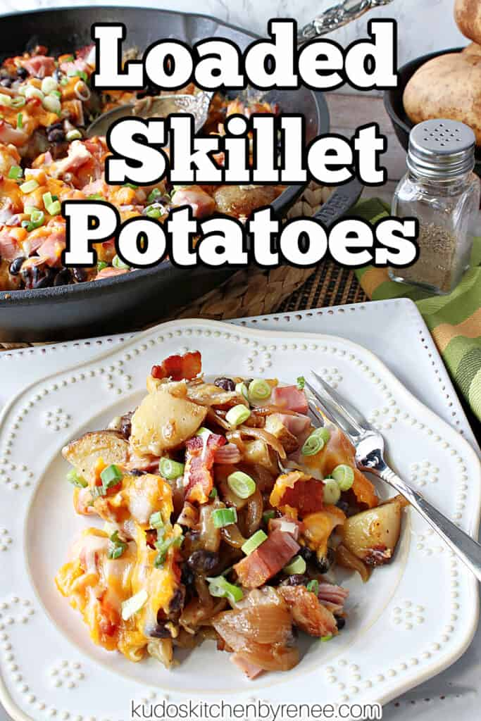 A vertical closeup along with a title text overlay graphic for Loaded Skillet Potatoes on a white plate along with a cast iron skillet in the background.