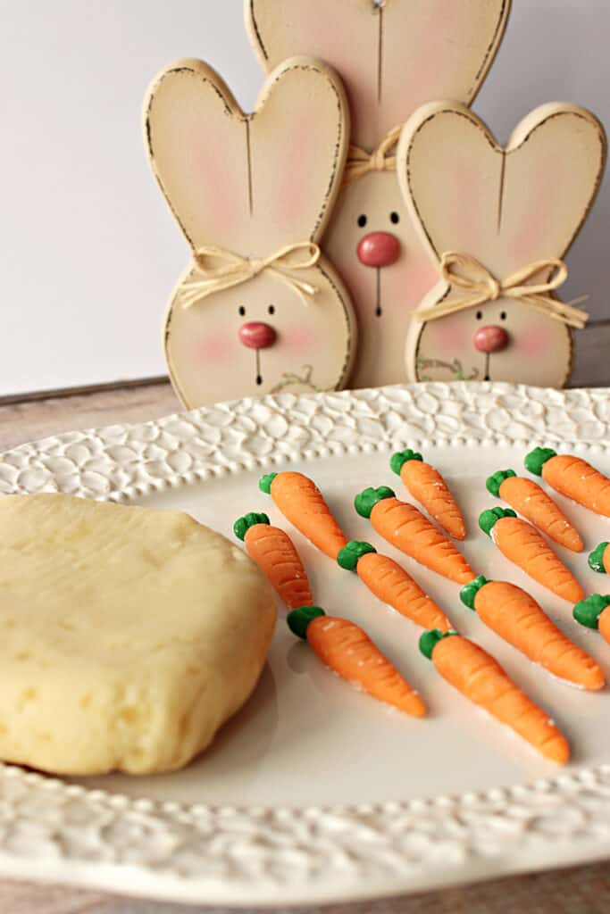 A vertical closeup image of a pretty platter with Homemade Marzipan Candy Carrots and a block of homemade marzipan along with some cute bunnies in the background.