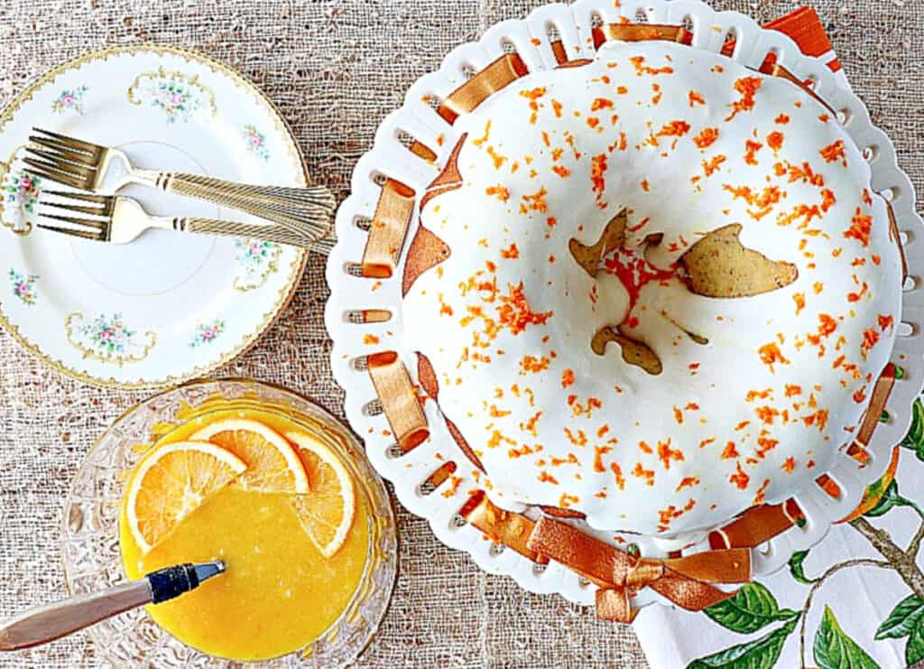 An overhead image of an iced Orange Bundt Cake with orange zest on top along with a bowl of orange curd on the side.