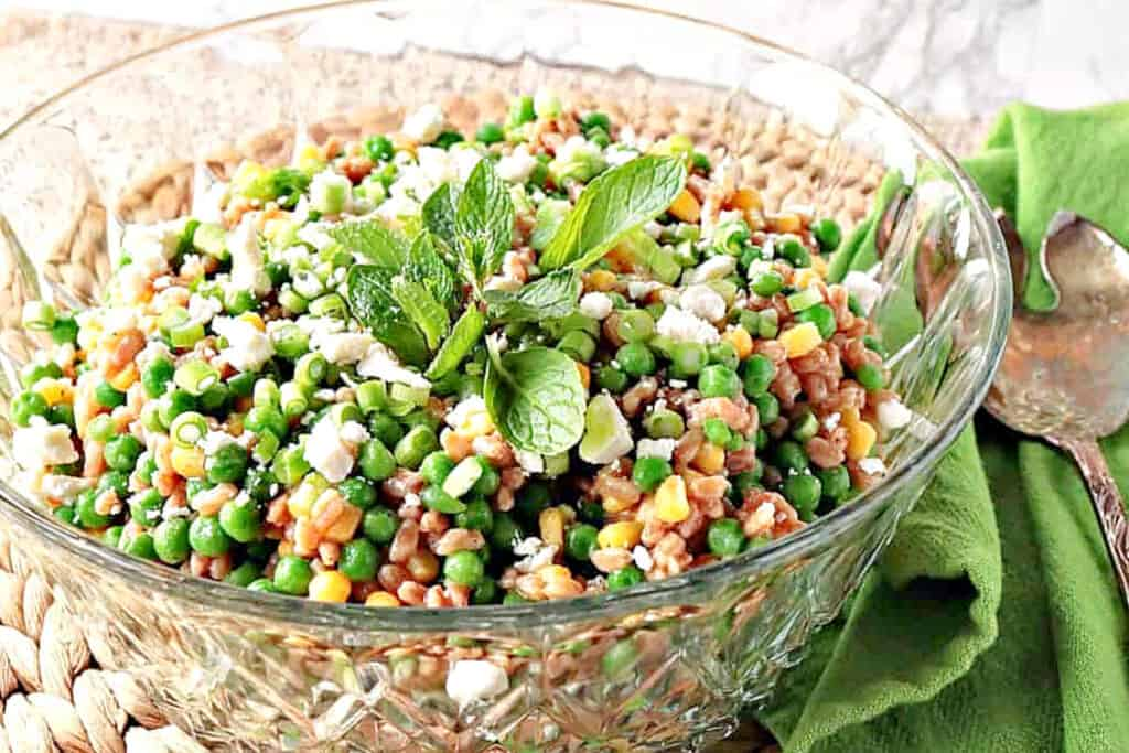 A horizontal offset photo of a glass bowl filled with Pea and Farro salad along with fresh mint and a green napkin on the side.