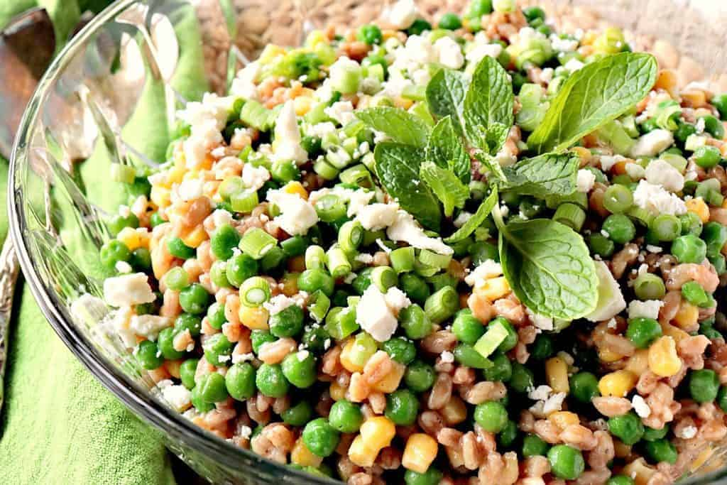 An offset horizontal photo of a Farro Salad with Peas and Scallions in a glass bowl with a green napkin and mint.