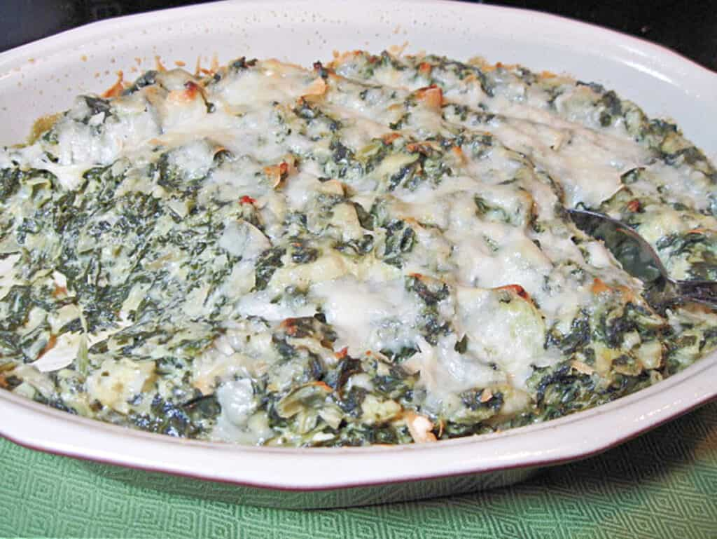 A oval baking dish filled with Spinach Artichoke Dip with melted cheese on top.