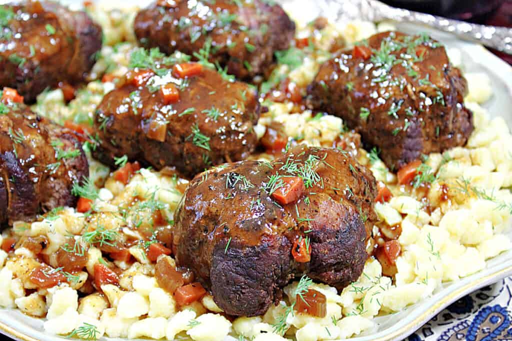 A closeup horizontal photo of German Beef Rouladen on a platter with gravy and fresh dill as garnish.