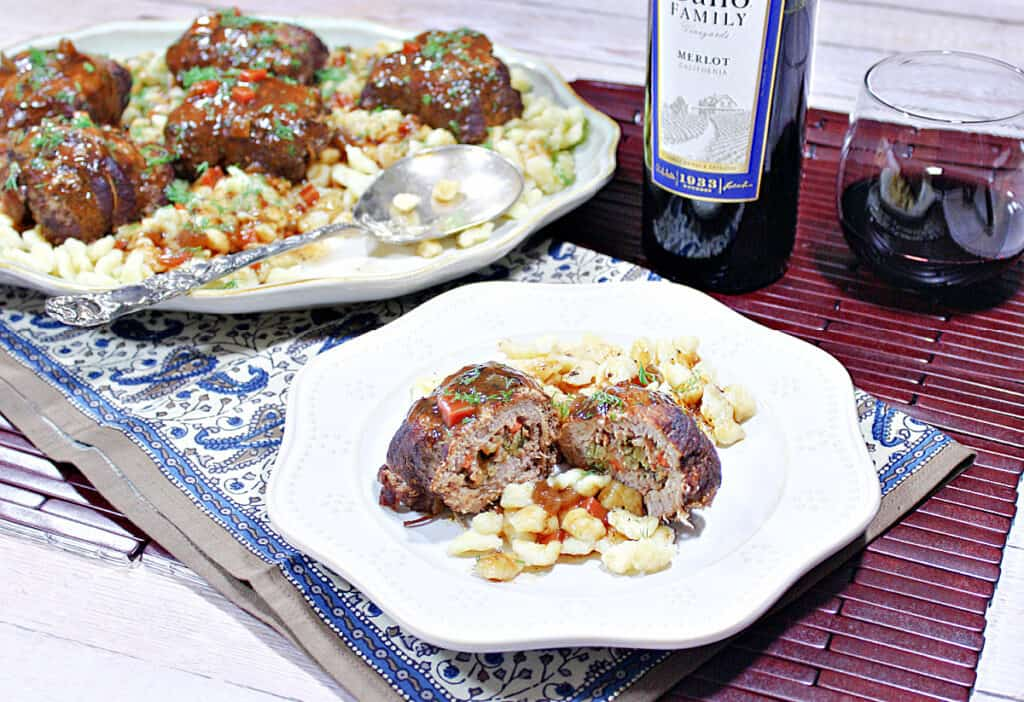 A dinner table set with a plate and a platter filled with Traditional German Beef Rouladen along with German spaetzle and a bottle of wine.