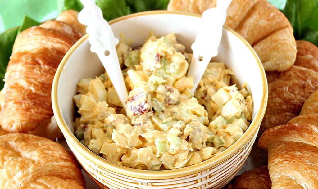 A overhead horizontal photo of Bacon Egg Salad in a yellow and white bowl with bunny spoons.
