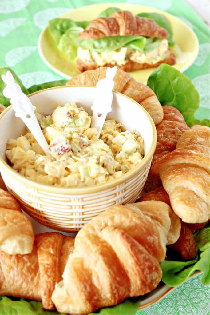 A small bowl with two bunny spoons filled with creamy Bacon Egg Salad surrounded by baked croissants.