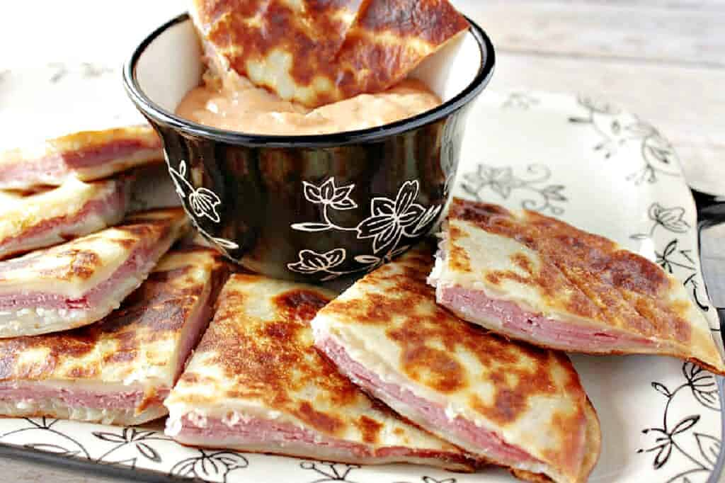 A tray of Rueben Quesadillas and some dipping sauce surrounded by a black and white napkin.