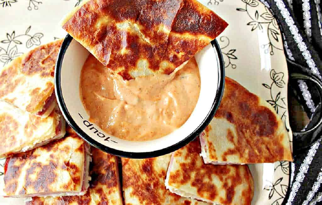 A direct overhead photo of a wedge of Reuben Quesadilla dipped into homemade sauce.
