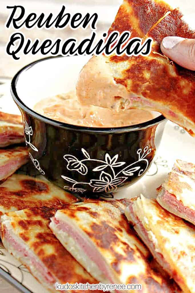 A vertical closeup of a hand holding a wedge of corned beef quesadillas dipped in sauce along with a title text overlay graphic in the corner.