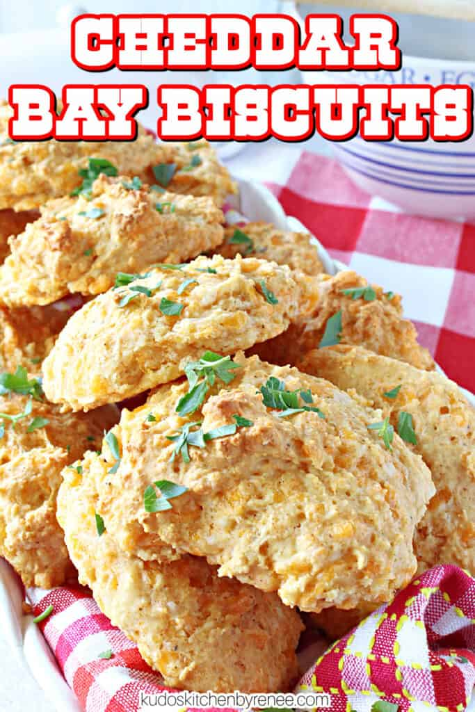 A closeup image of a cheesy Cheddar Bay Biscuits along with chopped parsley and also a title text overlay image.