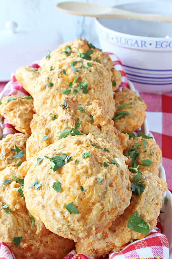 A vertical closeup of a basket of Better Cheddar Bay Biscuits topped with parsley.