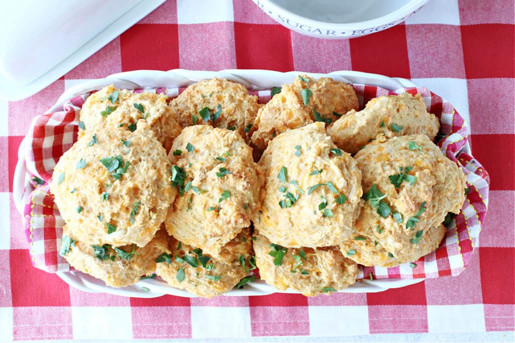 An overhead photo of a basket filled with a red and white checked napkin along with Cheddar Bay Biscuits topped with parsley.