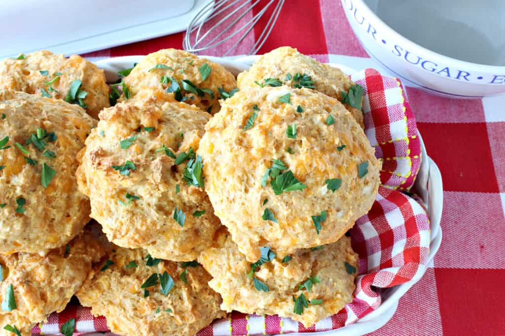 An overhead photo of a basket filled with Better Cheddar Bay Biscuits topped with fresh parsley and on a red and white checked napkin.