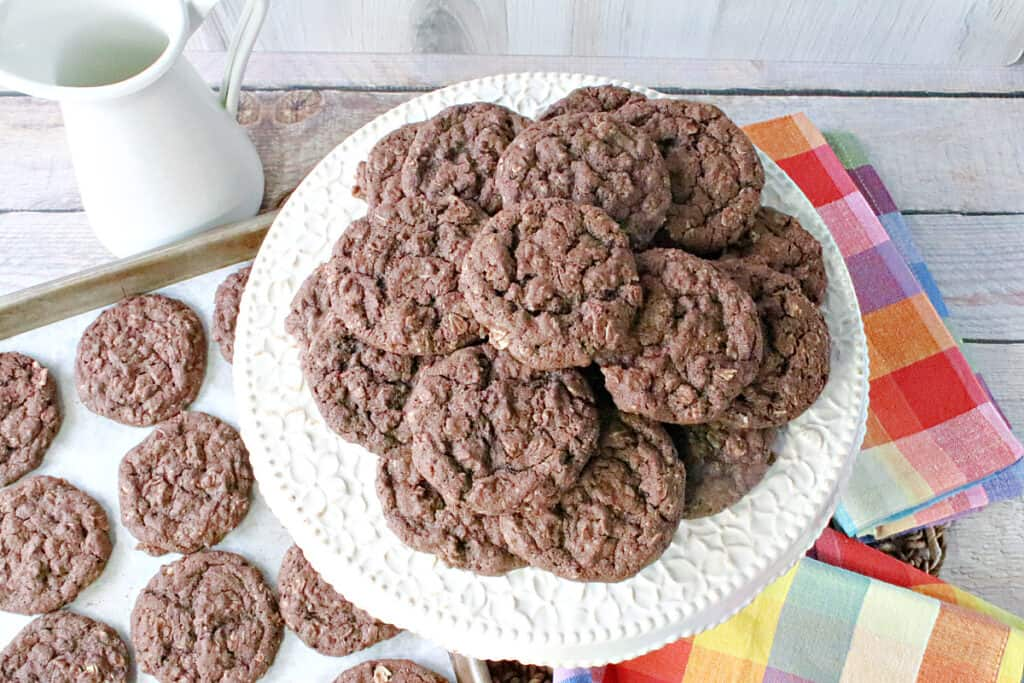 An overhead photo of a cake plate and a baking sheet filled with Chocolate Oatmeal Cookies along with a colorful napkin.