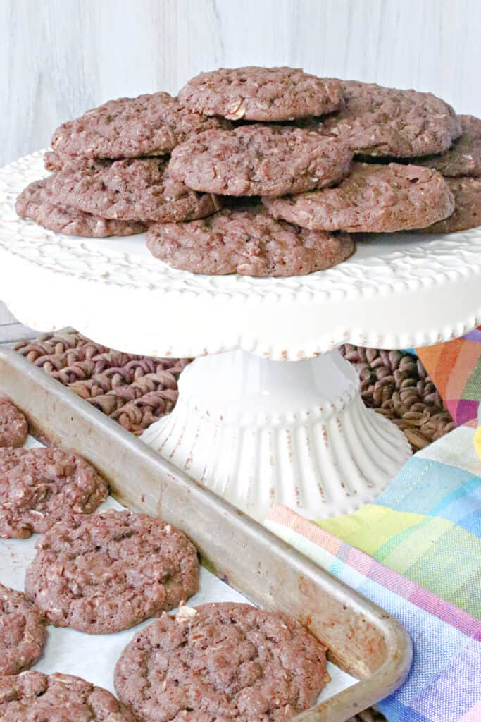 A vertical image of a cake plate filled with Chocolate Oatmeal Cookies along with a baking sheet filled with cookies and a colorful napkin.