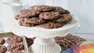 A white cake plate filled with Chocolate Oatmeal Cookies along with a colorful napkin in the foreground.
