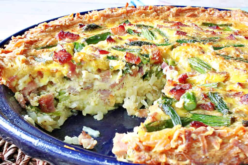 A horizontal closeup photo of a Ham and Asparagus Quiche with a slice taken out.