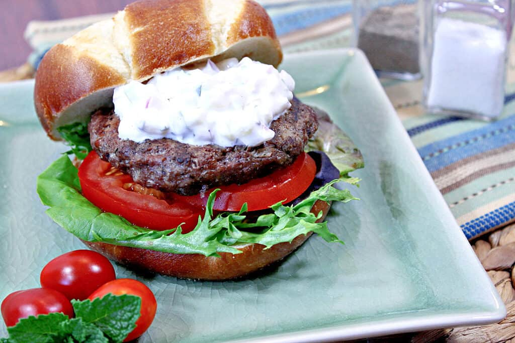 An offset horizontal photo of a Lamb Burgers with Feta and Tzatziki sauce on a green plate with tomatoes, lettuce, and a bun.