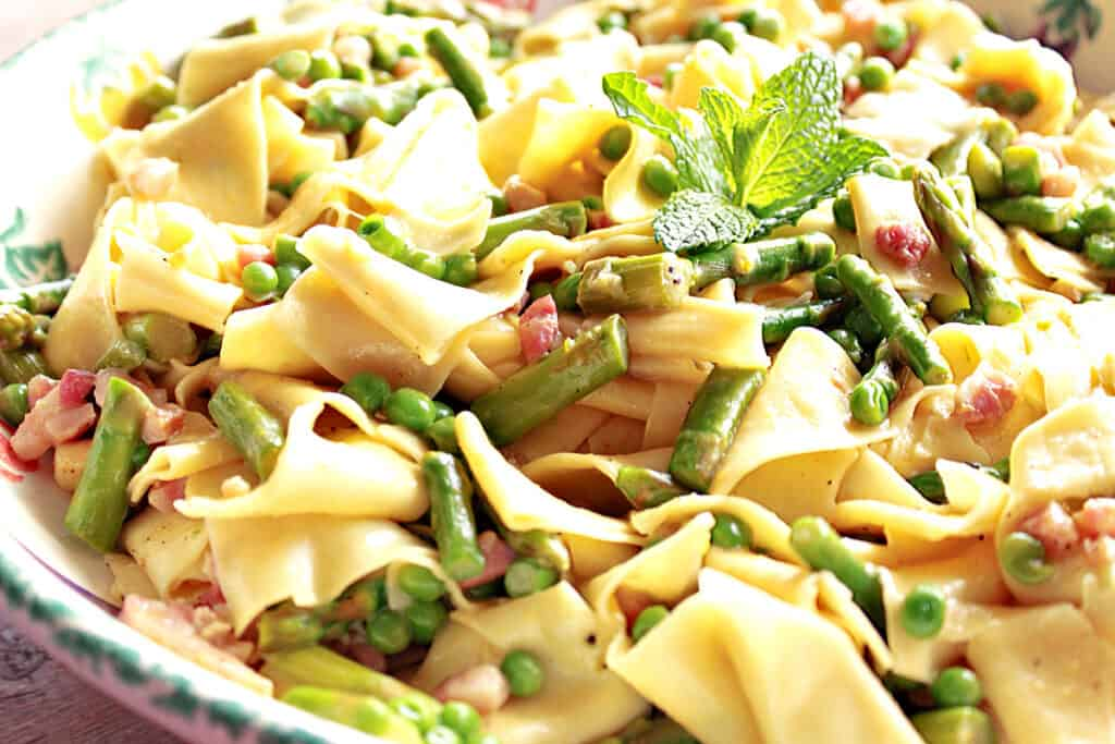 A closeup horizontal photo of a bowl filled with Pappardelle with Spring Vegetables like peas and asparagus.
