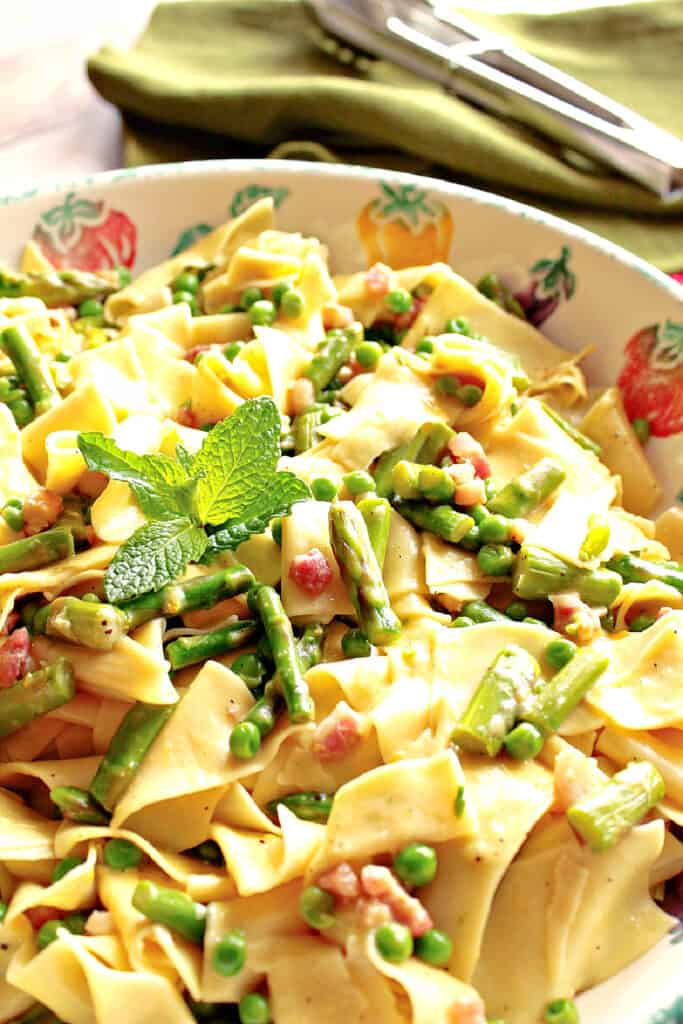 A closeup vertical image of Pappardelle with Spring Vegetables in a ceramic bowl with fresh mint, peas, asparagus, and pancetta.