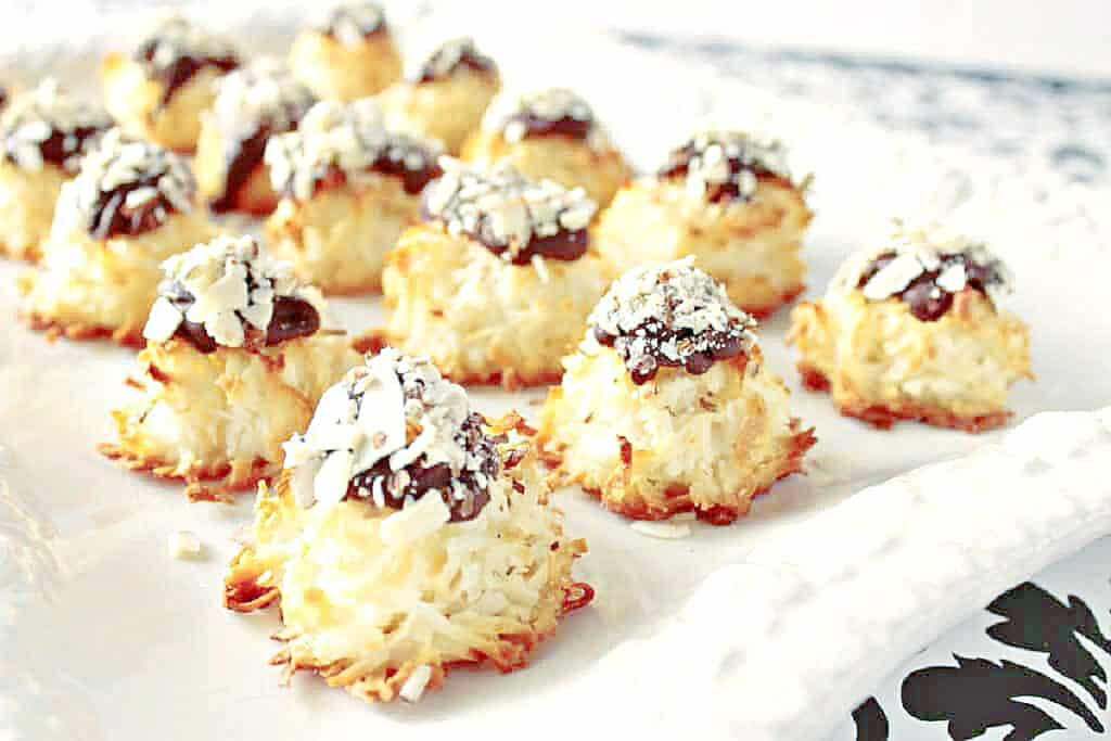 A white platter filled with Almond Joy Coconut Macaroons with chocolate tops and chopped nuts.
