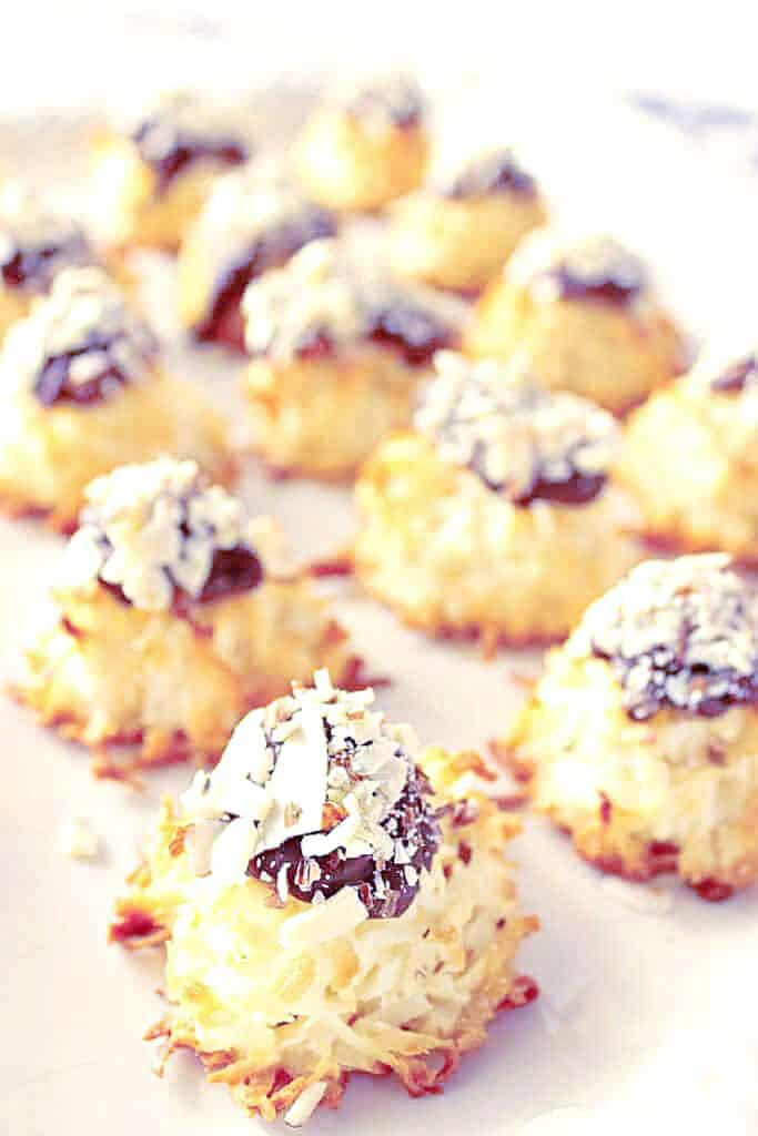 A vertical closeup photo of a tray of Almond Joy Coconut Macaroons along with a chocolate dollop and chopped nuts.