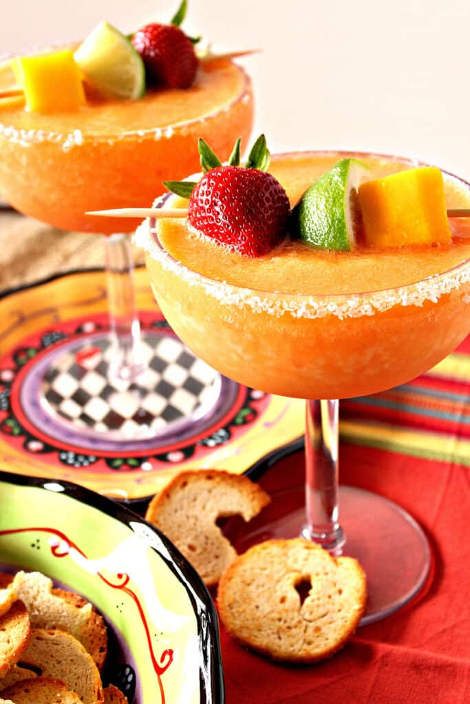 A vertical closeup of two delicious Frozen Mango Strawberry Margaritas in salt-rimmed glassed with fresh fruit as garnish.