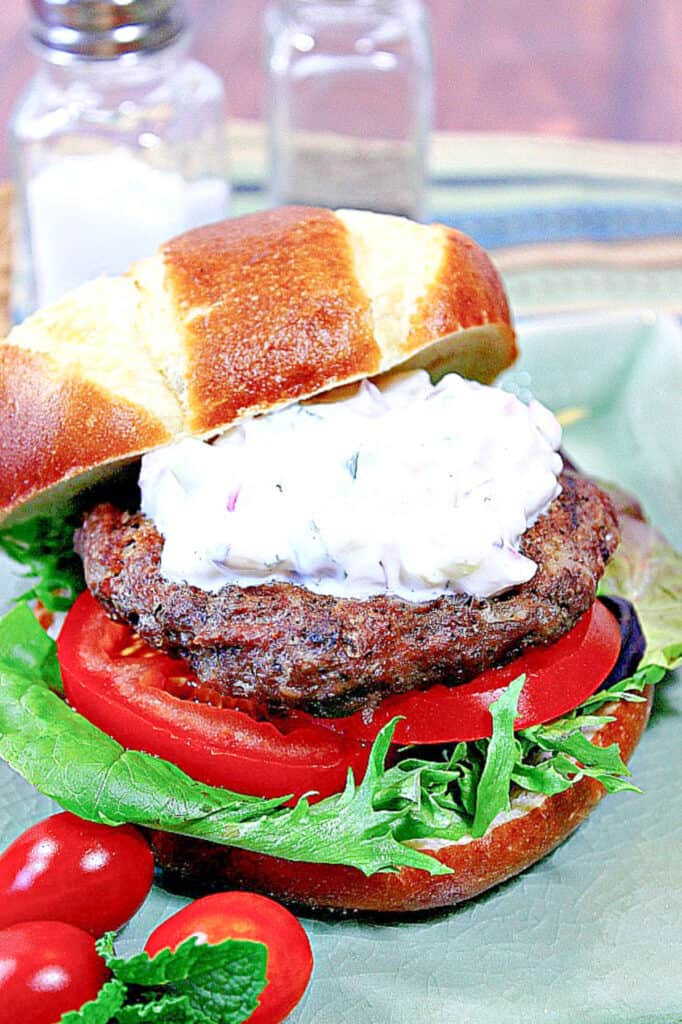 A colorful vertical image of a Lamb Burger with Feta and Tzatziki on a pretzel bun along with lettuce and tomatoes.