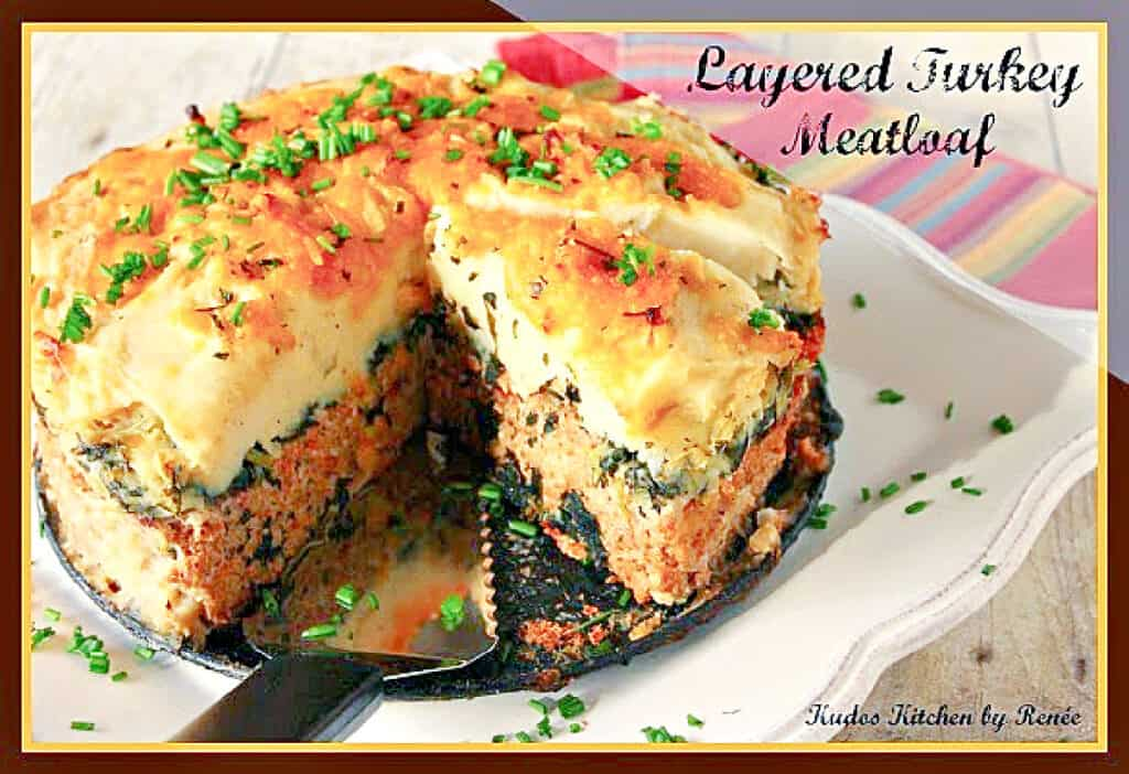 A horizontal photo of a Layered Turkey Meatloaf on a square platter with a serving spatula.