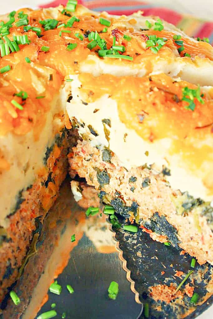A vertical closeup photo of a Layered Turkey Meatloaf with mashed potatoes and melted cheese on top.