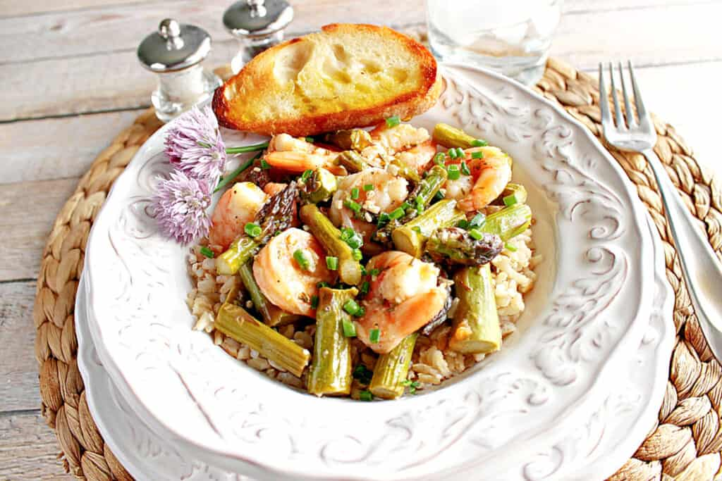 A pretty white bowl filled with Shrimp and Asparagus along with chives, garlic bread, and clover flowers.