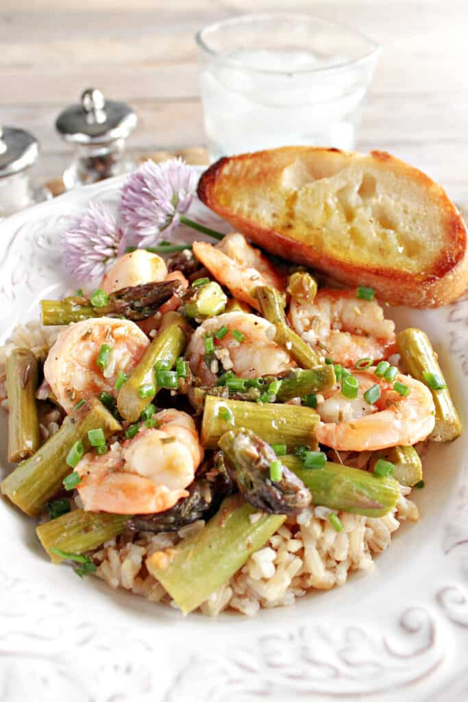 A vertical closeup image of Shrimp and Asparagus in a bowl with a piece of garlic bread and some clover flowers.
