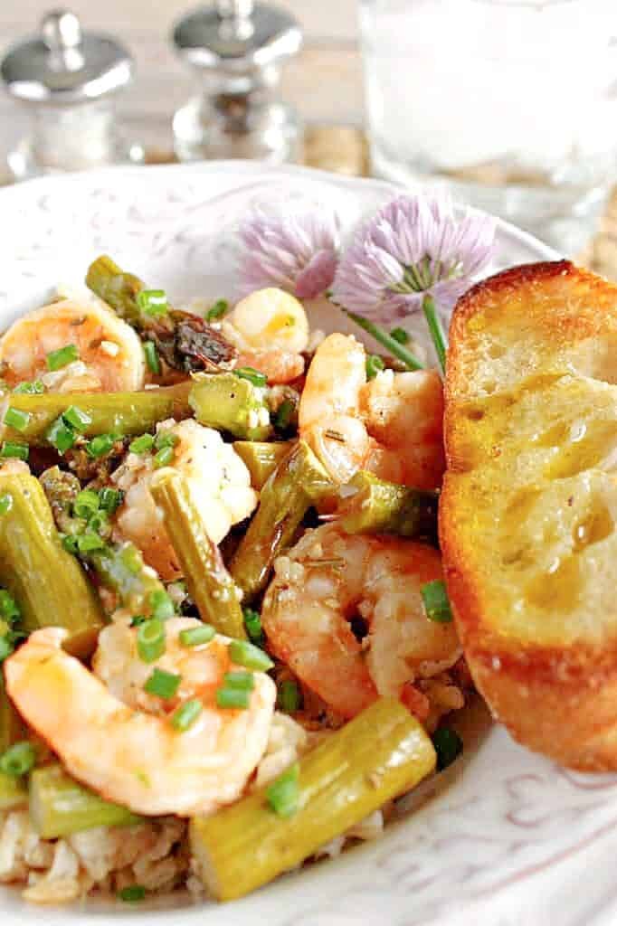 A vertical closeup photo of Shrimp and Asparagus along with chives and garlic bread.