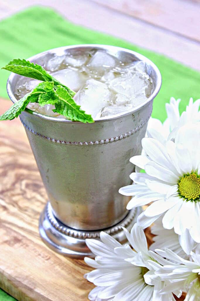 A vertical closeup photo of a Traditional Mint Julep in a sliver metal cup along with ice and fresh mint leaves.