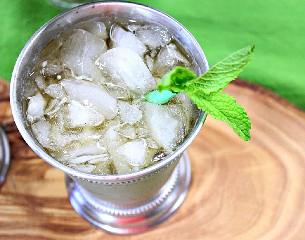 A horizontal photo of the inside of a metal glass cocktail glass filled with a Traditional Mint Julep with crushed ice and fresh mint.