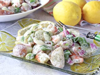 A glass plate filled with Dilled Cucumber Salad with Shrimp along with a fork and lemons in the background.