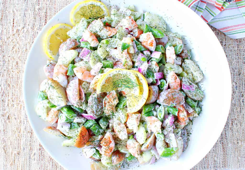 A direct overhead image of Dilled Cucumber Salad with Shrimp in a round white bowl topped with dill and lemon slices.