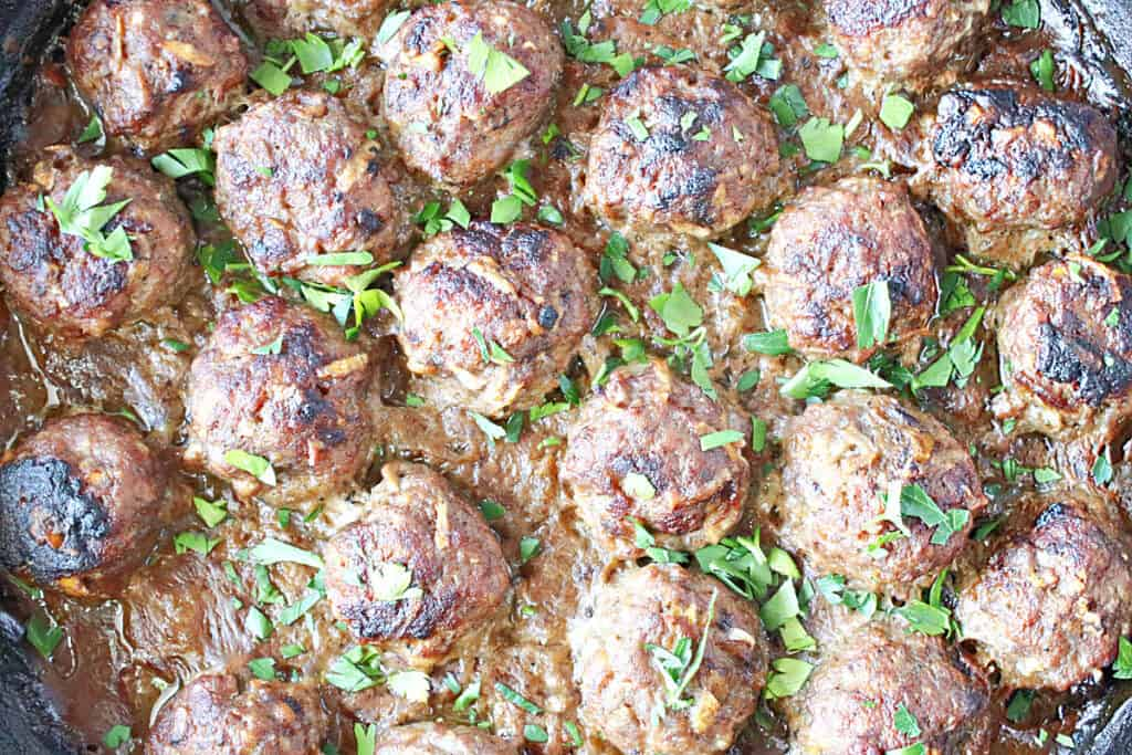 Overhead closeup image of Pork Meatballs with Apple and Onion in a skillet with chopped parsley as garnish.