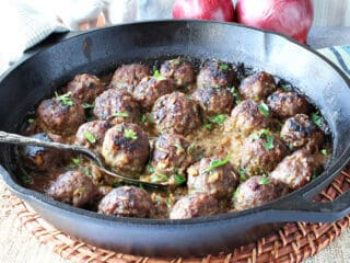 A cast iron skillet filled with Pork Meatballs with Apple and Onion and a serving spoon.