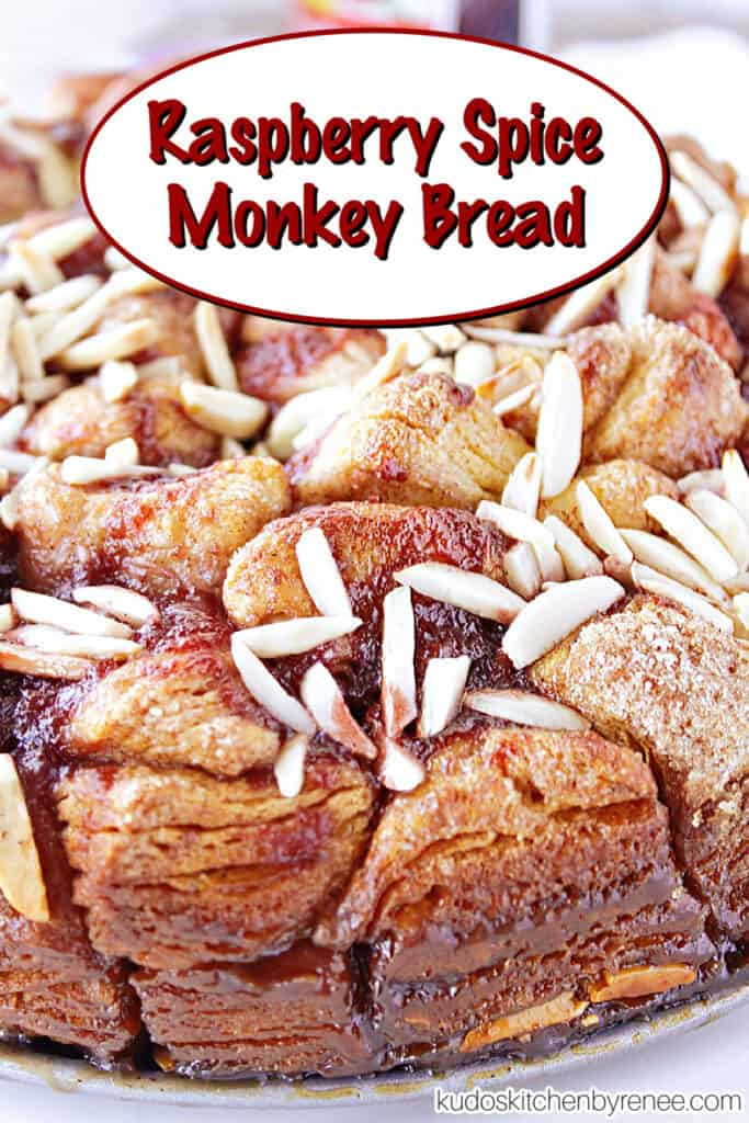 A vertical closeup along with a title text overlay graphic for Raspberry Spice Monkey Bread with a cinnamon sugar coating, raspberry jam, and almonds.