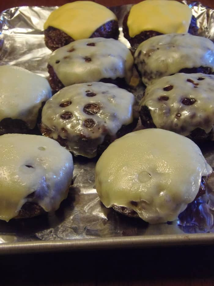 A vertical closeup of a bunch of cheese covered burgers stuffed with caramelized onions.