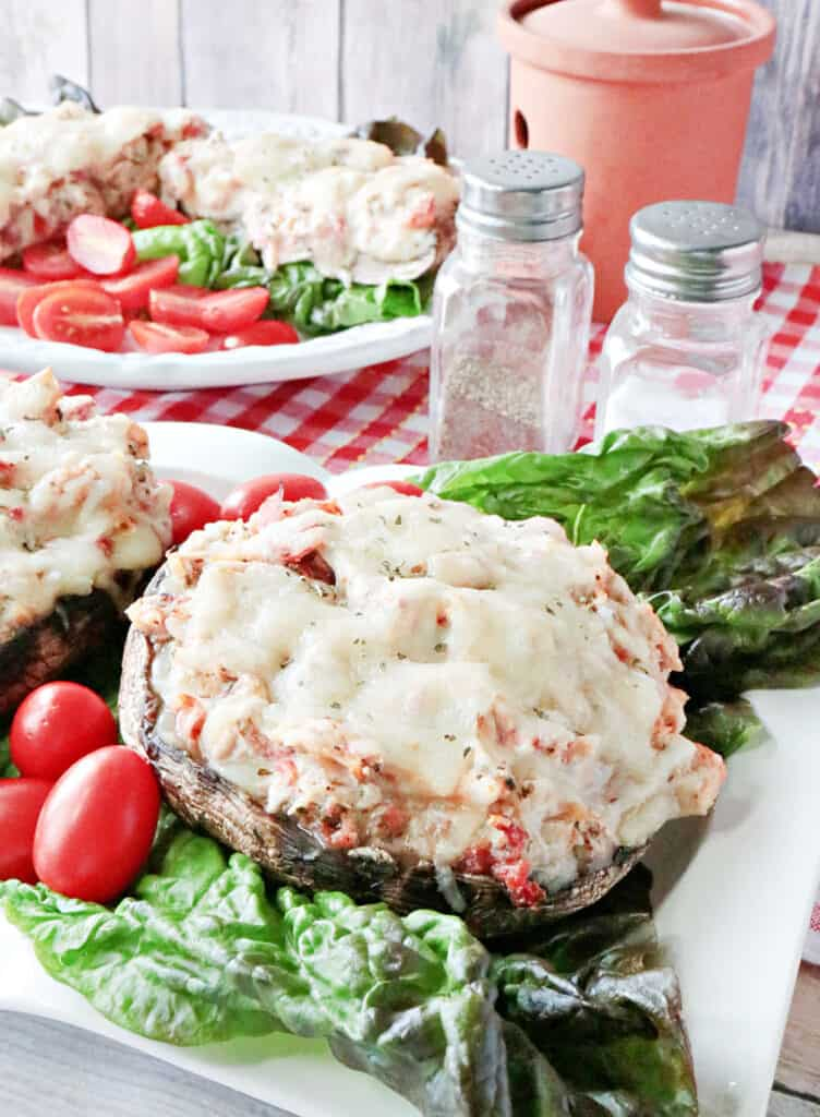 A closeup vertical photo Chicken Parmesan Stuffed Portobellos, one in the foreground and one in the background cut in half.