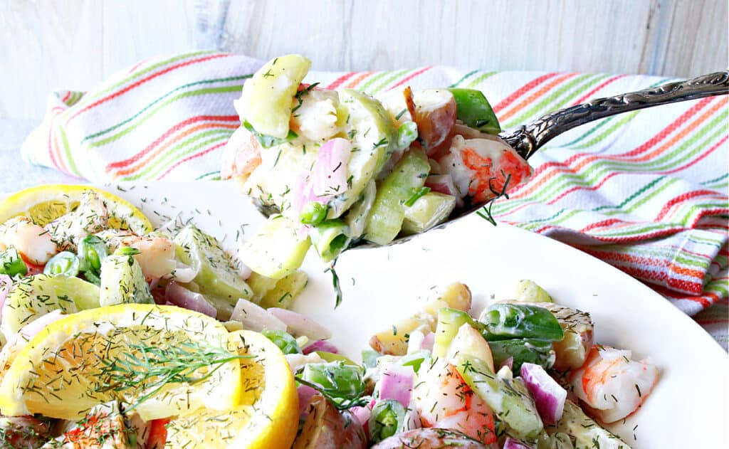 A closeup horizontal image of a spoonful of Dilled Cucumber Salad with Shrimp with a colorful napkin in the background.
